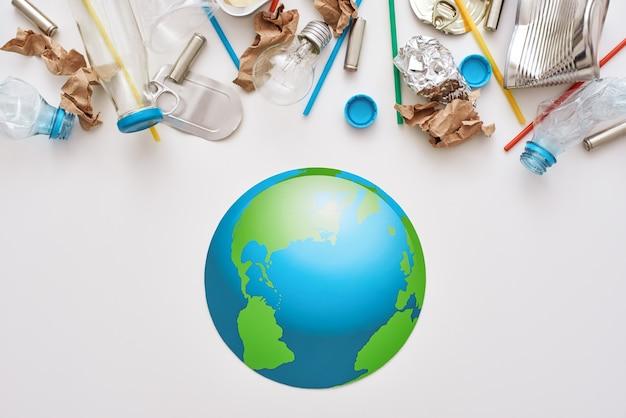 Мир в опасности. мусор атакует земной шар. пластик, банки, бумажный мусор перемешиваются вместе