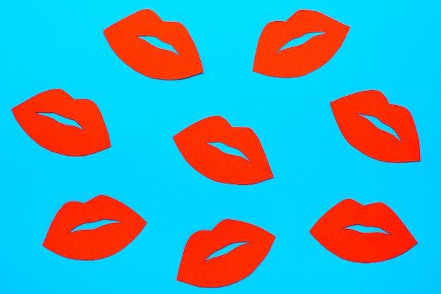 Всемирный день поцелуев. много красных губ из картона на синем фоне