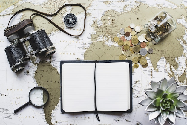 World map background with blank notebook and binoculars