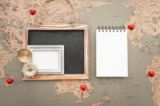World map background with blank notebook and travel items
