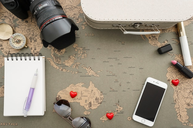 World map background with a collection of travel items