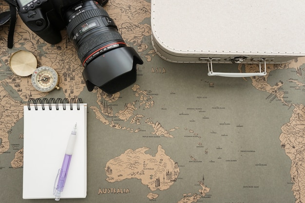 World map background with notebook and other travel objects