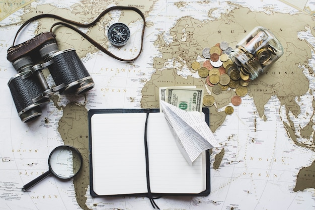 World map background with variety of travel objects