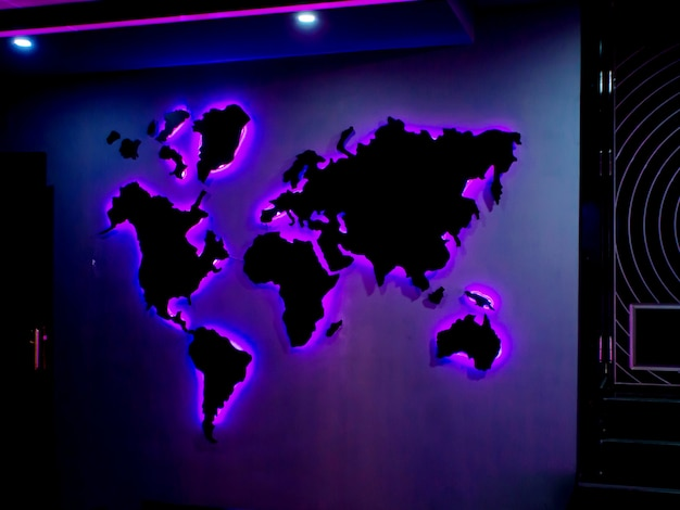 World map installed on the wall with purple neon lights in the dark room
