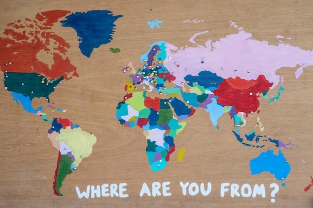 나무 벽 배경에 여러 가지 색의 페인트로 칠해진 세계 지도와 당신은 어디에서 왔는지 비문