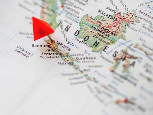 Карта мира с упором на республику индонезия. красный треугольный штифт на столице джакарте.