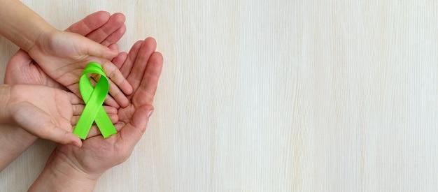 Всемирный день осведомленности о психическом здоровье руки взрослых и детей держат зеленую ленту