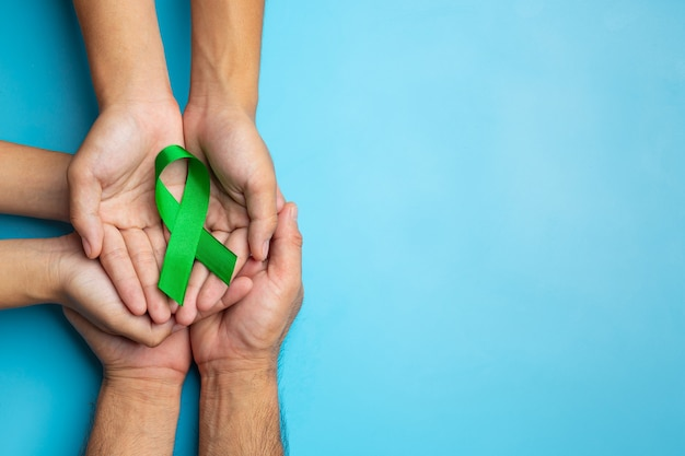 World mental health day. green ribbon put in human's hands on blue background