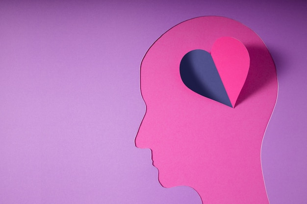 World mental health day. paper cut as human head with heart instead the brain. psychology