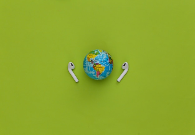 세계 음악의 날. 녹색 배경에 글로브 및 무선 헤드폰입니다.