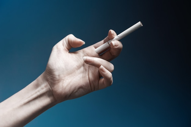 World no tabacco day. a pale, crooked female hand, close-up, holding a new cigarette. dark blue background. the concept of nicotine addiction.