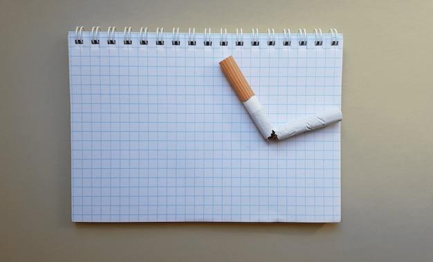 세계 금연의 날, 금연의 날. 비즈니스 노트북에 깨진 담배, 텍스트를 위한 장소.