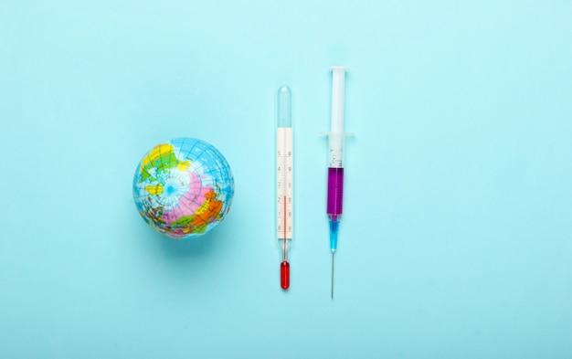 世界的大流行。予防接種。青い背景に温度計と注射器を備えた地球儀。世界的なエピデミック