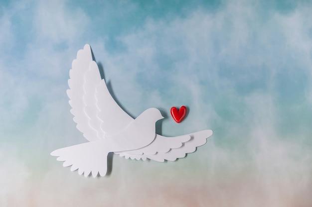 Всемирный день мира шаблон поздравительной открытки. силуэт голубя, перевозящих красное сердце.