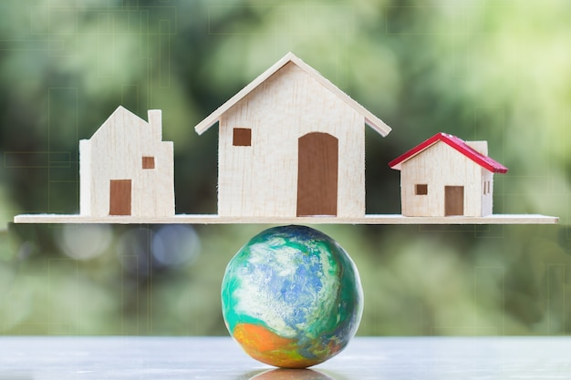 World of property real estate investment concept : wooden homes placed on global scale with balance / green background. business investments and mortgage become everyone life needs