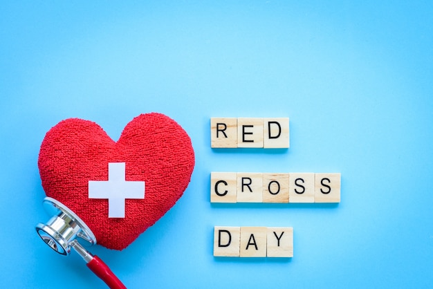 World red cross day, red heart with stethoscope on blue background.