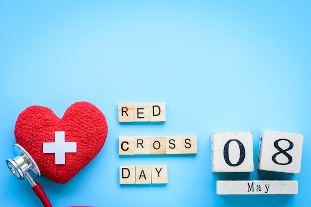 World red cross, may 8. healthcare concept. red heart with stethoscope on blue background.