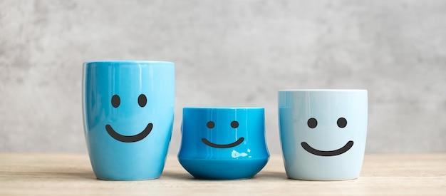 세계 미소의 날과 국제 커피의 날 개념. 고객 리뷰를 위한 블루 커피 컵의 행복한 얼굴. 서비스 등급, 순위, 만족도 및 피드백