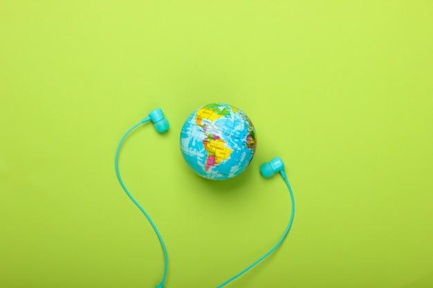 世界の歌。グローバルミュージックチャート。地球の音楽。緑の壁にステレオイヤホンと地球儀上面図