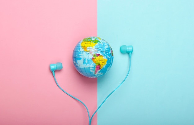 世界の歌。グローバルミュージックチャート。地球の音楽。ピンクブルーの壁にステレオイヤホンと地球儀上面図