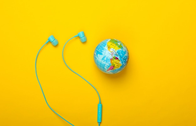 世界の歌。グローバルミュージックチャート。地球の音楽。ステレオイヤホンと黄色の壁に地球儀上面図