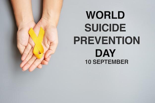世界自殺予防デー、生きている人々と病気をサポートするためのイエローリボンを手に持って