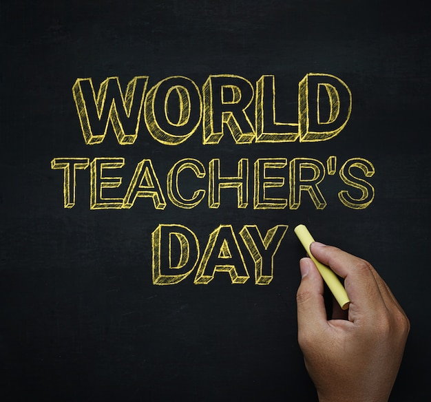 World teacher's day male hand writing on blackboard