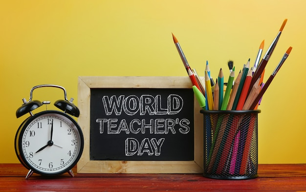 World teacher's day text. alarm clock, blackboard and school stationary in basket
