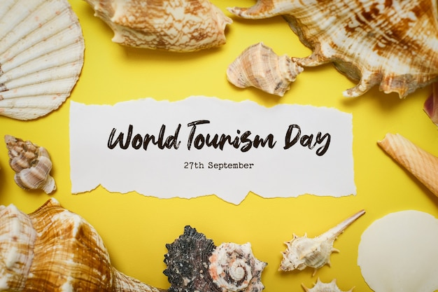 World tourism day incription over yellow background, with palm leaves, clam shell, and shoes flat lay background