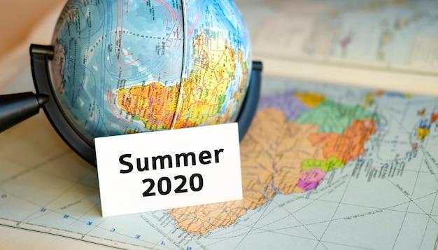 2020年夏の世界観光-アトラスマップの背景にある小さな地球の白いシート上のテキスト