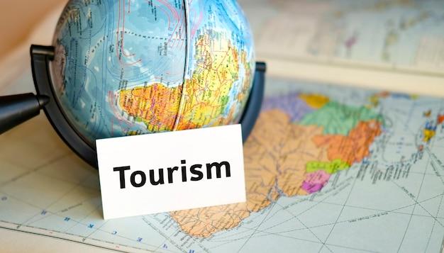 Мировой туризм - текст на белом листе в маленьком глобусе на фоне карты атласа