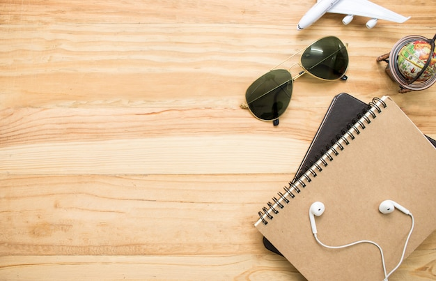 World travel equipment such as sunglasses, notebooks, maps.
