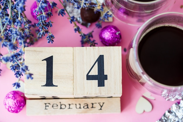 World valentine's day. wooden calendar with date 14 february on pink background with coffee and sweets