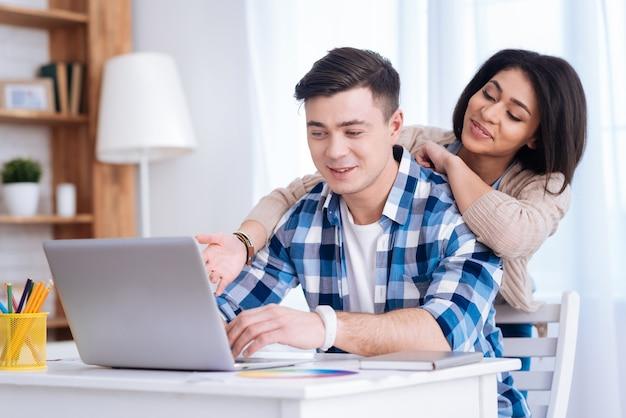 ワールドウェブ。男が入力しながら画面を見ている肯定的な愛情のあるカップル