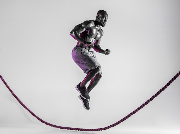 Above the world. young african-american bodybuilder training on grey studio background. muscular male model in sportwear jumping over battle rope. concept of sport, bodybuilding, healthy lifestyle.
