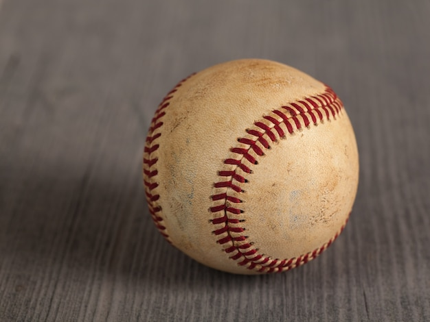 Worn baseball on the wooden table
