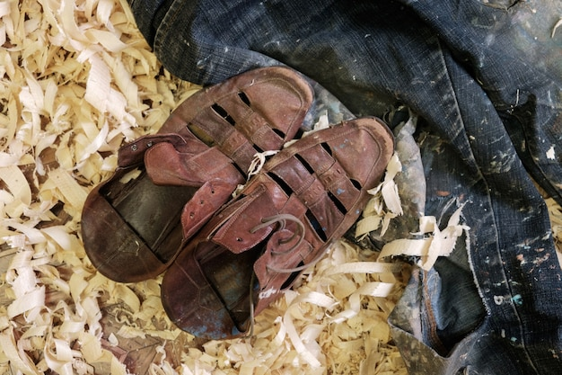 Worn leather shoes and ripped jeans on the chips of wood in the workshop of the painter