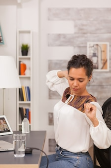 지친 여성 프리랜서가 홈 오피스에서 노트북 작업을 하는 동안 등을 쭉 뻗고 있습니다.