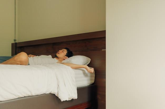 使い古された男はベッドで寝ます。疲れや疲れの概念。