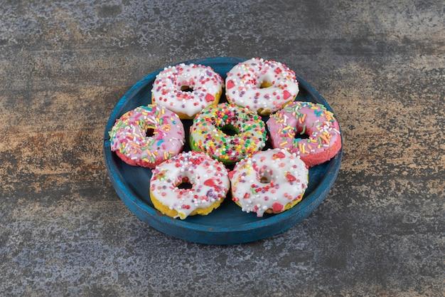 나무 표면에 사탕을 뿌린 도넛과 함께 낡은 플래터
