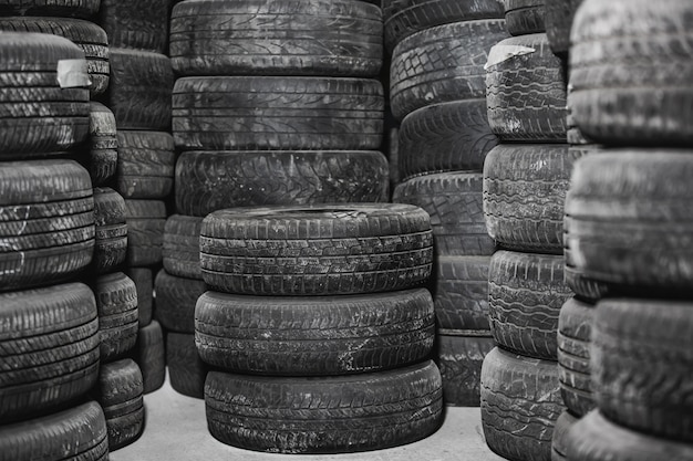 Worn out or used car tires in warehouse, service center, transportation concept