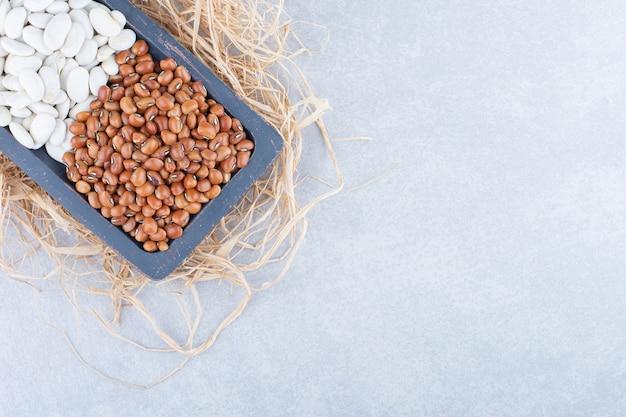 Изношенное деревянное блюдо на груде соломы, наполненное красной фасолью и темно-синей фасолью на мраморной поверхности