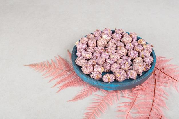 大理石のテーブルの上のピンクの葉の束の上に置かれている風味のあるポップコーンの使い古された木製トレイ。