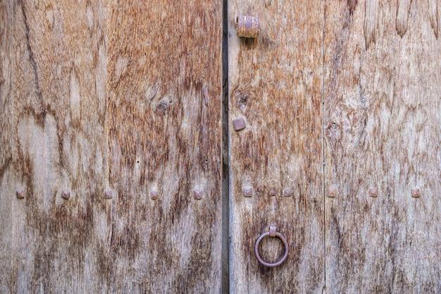 Изношенная деревянная дверь с ручкой-серьгой. винтажная концепция