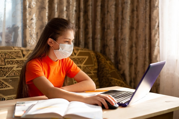 Молодая школьница в медицинской маске, обучение на дому, делать домашнее задание в школе, писать в блокноте, worning на ноутбуке онлайн. коронавирусный карантин. дистанционное обучение
