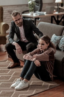 Worried about daughter. businessman wearing dark suit and glasses feeling worried about stressed daughter