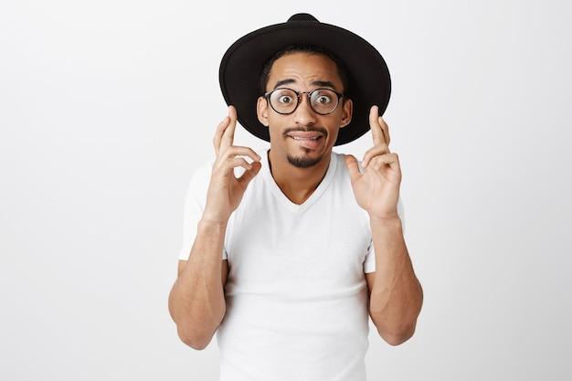 Preoccupato ragazzo afro-americano in cappello hipster e maglietta casual incrocia le dita buona fortuna, esprimendo un desiderio