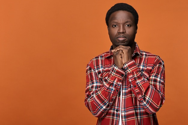 Studente maschio afroamericano preoccupato in camicia a scacchi rossa che tiene le mani giunte sotto il mento, con un'espressione facciale seria, nervoso mentre aspetta i risultati dell'esame al college
