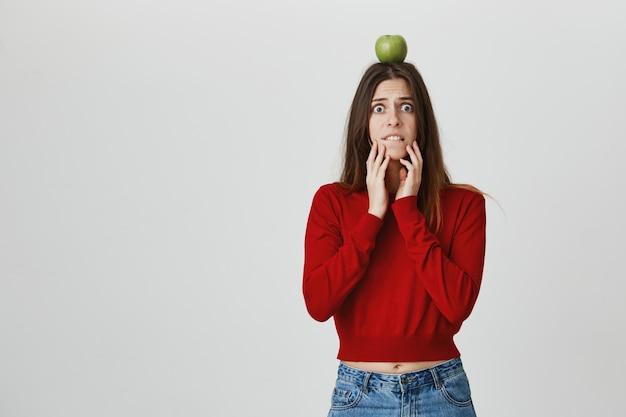 La ragazza graziosa preoccupata e allarmata che tiene l'obiettivo della mela sulla testa e che aspetta l'arciere rende il colpo, labbro mordace nervoso