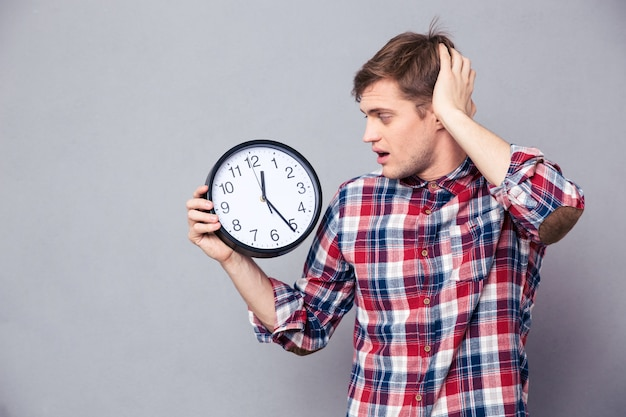 Worried amazed young man in checkered shirt holding and looking at clock over grey wall